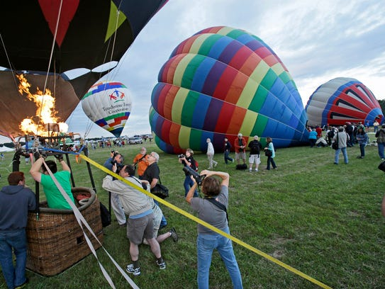 People photograph hot air balloons being inflated at