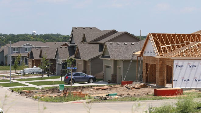 Workers build a home in Rock Creek Crossing near Northwest Fifth and Northwest Weigel Drive in this 2014 file photo. There has been significant growth in the Ankeny community over the last several years, pushing the city above 62,000 people and into its new spot as the ninth-largest city in Iowa.