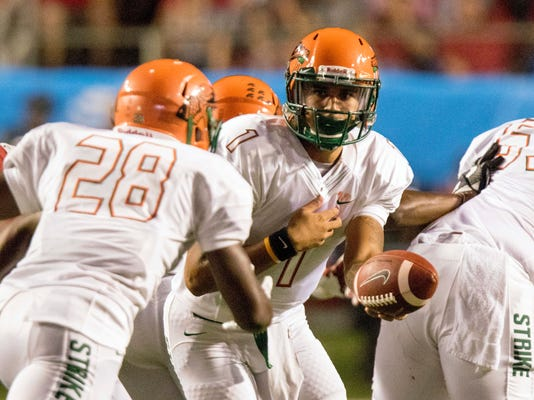 Florida A&M quarterback Vincent Jeffries, 1, hands the ball off to running back Ricky Henrilus, 28, during the first quarter of an NCAA college football game against Arkansas on Thursday, Aug. 31, 2017, in Little Rock, Ark.. (AP Photo/Gareth Patterson)
