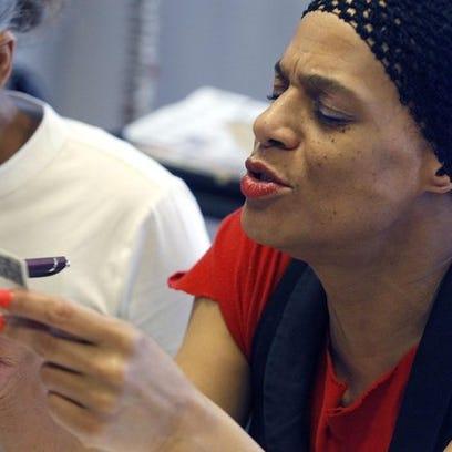 Poll worker Kim Tinsley checks a photo identification