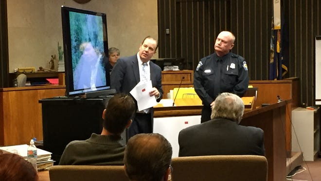 Macomb County Assistant Prosecutor William Dailey, left, and Armada Police Officer Phil Neumeyer look at a photo of the Macomb Orchard Trail during the murder trial of James VanCallis. The screen was later turned for jurors and pertinent personnel, such as attorneys, the judge and VanCallis, to see crime scene photos of how April's body was found July 24, 2014.