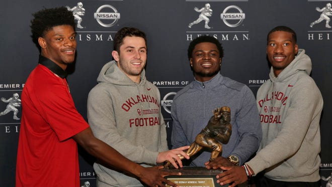 Heisman Trophy finalists, from left: Louisville's Lamar Jackson, Oklahoma's Baker Mayfield, Michigan's Jabrill Peppers, and Oklahoma's Dede Westbrook, poses with the award in New York, Friday, Dec. 9, 2016.