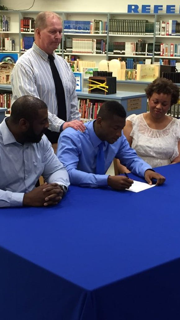 Ernest Shockley (center) signs his letter of intent to play football at Division II Bowie State. He is surrounded by his parents and Stephen Decatur head football coach, Bob Knox.