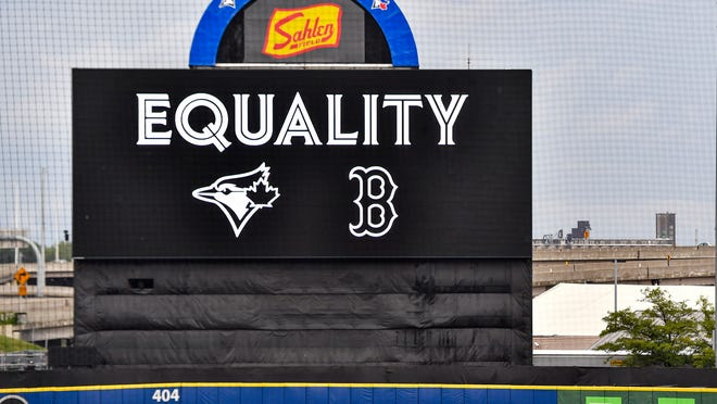 """The scoreboard read """"Equality"""" as a Boston Red Sox player warms up in the outfield at Sahlen Field before a baseball game against the Toronto Blue Jays in Buffalo, N.Y., Thursday, Aug. 27, 2020."""