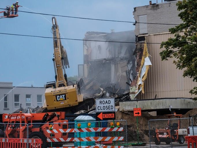 A demolition crew starts work on a former bank in the