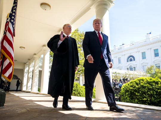 Supreme Court Justice walks with President Trump at the White House in April 2017.