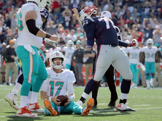 New England Patriots defensive tackle Adam Butler, right, celebrates after sacking Miami Dolphins quarterback Ryan Tannehill (17) on Sept. 30, 2018.