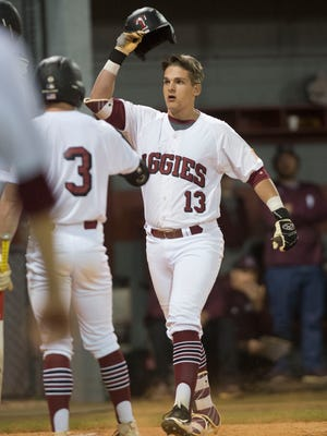 Tate High School's Logan Blackmon celebrates his first inning home run with his team mates after crossing the plate during Thursday night final game of the Aggie Classic.