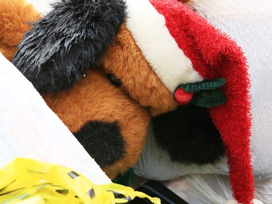 A stuffed animal with a Santa hat sits atop a garbage