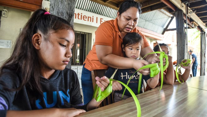 Saina Donna Cruz, standing, teaches young students how to weave with coconut leaves at the Chief Hurao Academy in Hagåtña in March 9, 2017.