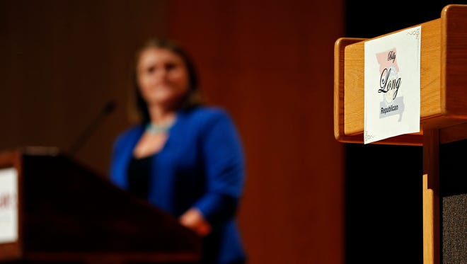 A podium intended for incumbent U.S. Representative for Missouri's 7th District Billy Long stands empty besides Genevieve Williams, his Democratic opponent, during a debate hosted at the Plaster Student Union in the Missouri State University campus in Springfield, Mo. on Oct. 26, 2016.