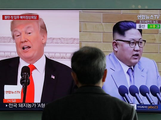 A man watches a TV screen showing file footage of U.S. President Donald Trump, left, and North Korean leader Kim Jong Un, right, during a news program at the Seoul Railway Station in Seoul, South Korea.