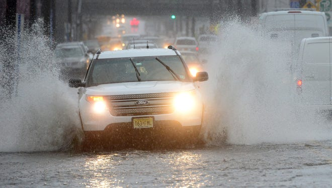 An SUV speeds through the flood waters on Hudson St in Hackensack on Monday morning April 16, 2018.