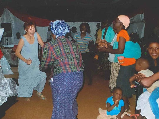 Sally Potts dances with local villagers during her