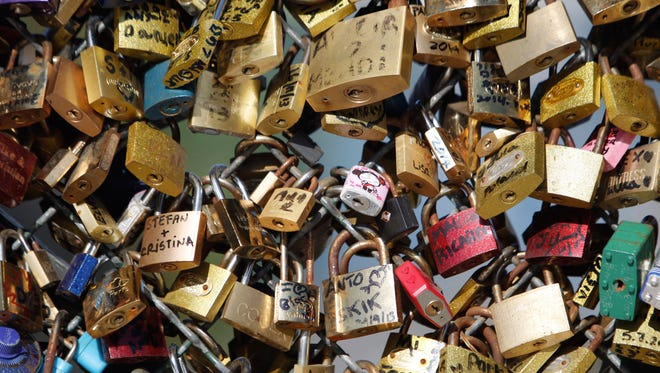 Love locks fixed on the Pont des Arts bridge in Paris. Any hope that the padlocks that cling to Paris' famed bridge would last forever  will be dashed by city hall, who plan to dismantle them June 1, 2015.