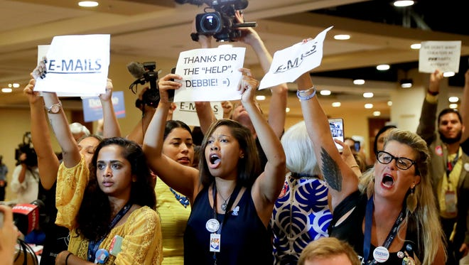 Protesters yell as DNC Chairwoman, Debbie Wasserman Schultz arrives for a Florida delegation breakfast in Philadelphia, during the first day of the Democratic National Convention.