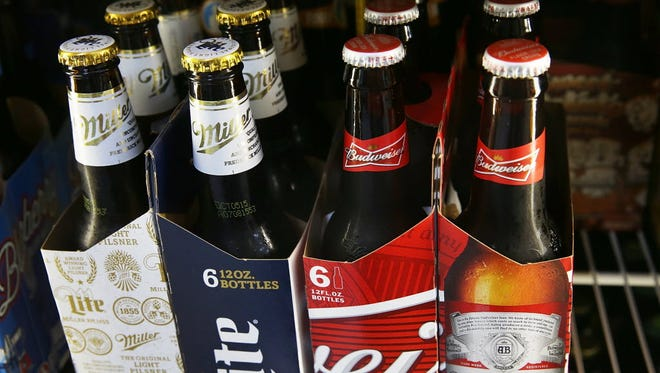 Bottles of Budweiser and Miller Lite beer are seen on Sept. 16, 2015, in Miami, Florida. Budweiser and Miller Lite are owned by Belgium's Anheuser-Busch InBev.