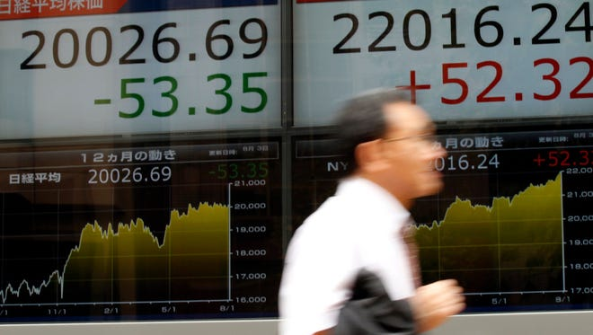 A man hurries past an electronic stock board of a securities firm in Tokyo on Aug. 3.