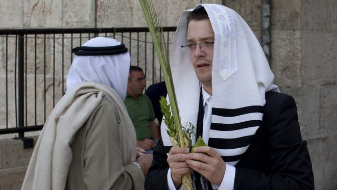 A Jewish man holds plants used during the Jewish holiday of Sukkot.