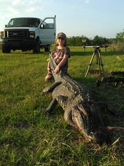 Maddie Marsh with a giant alligator she killed in Florida.