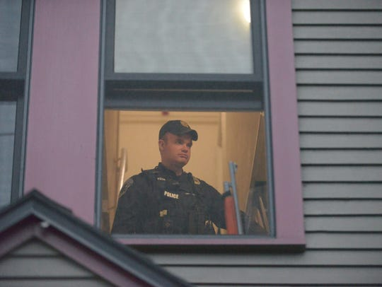 A Burlington police officer is seen through a second-floor