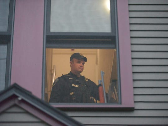 A Burlington police officer is seen through a second-floor window at 221 Pine St. during a standoff Thursday night, June 9, 2016, with a distraught woman.