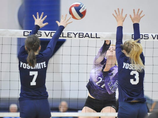 Christa Pilgrim spikes the ball past Yosemite in a Central Section Division III girls volleyball championship game at COS on November 11, 2017