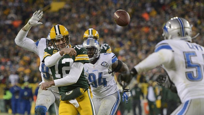 Green Bay Packers quarterback Aaron Rodgers (12) makes a touchdown pass to teammate Randall Cobb in the second quarter during Sunday's game against the Detroit Lions at Lambeau Field. Rodgers was injured on the play.