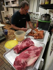 Mark Lammar rubs spices onto beef brisket before it is smoked Wednesday at Lammar's Smokehouse BBQ in Marshfield.