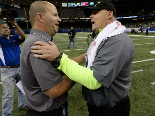 Head coach John Bachman Sr. meets CAtholic High head coach Brent Indest after the Cavaliers defeated the Panthers 27-24 in the 2014  LHSAA Division III finals game at the Superdome in New Orleans.