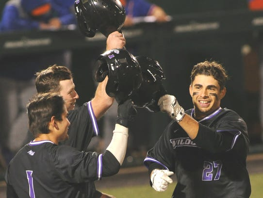 ACU's Matt Munoz, right, is greeted at home plate after