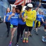 Survivors of the  Boston Marathon bombing April 15, 2013, carry the One Run for Boston baton to the finish on Sunday.
