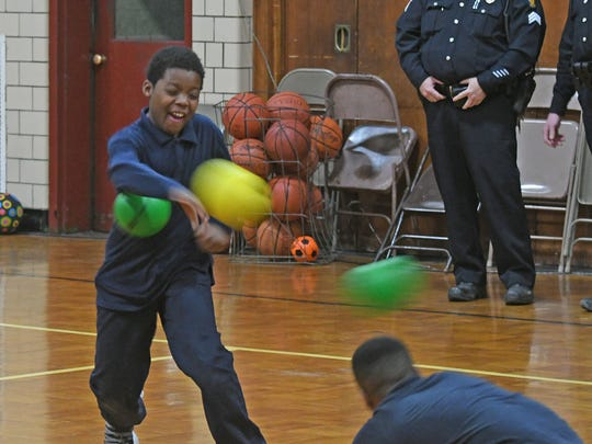 D.J. Corbin, 9 years old, gets hit as he throws the ball during a dodgeball game with members of law enforcement Thursday afternoon at the Friendly House.