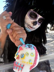 Santa Teresa resident Michelle Padilla applies frosting a sugar skull during a past Dia de las Muertos celebrations in Mesilla. This year, Day of the Dead events and altar building will be Oct. 28-30 on the Mesilla Plaza, followed by a costumed cemetery procession at dusk on Nov. 2.