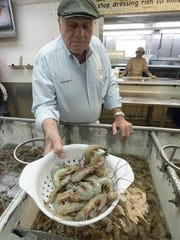 Frank Patti, owner of Joe Patti's Seafood, shows off