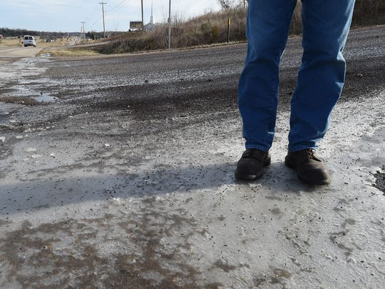 Chris Huett, Baxter County Road and Bridge superintendent, looks over an icy patch at the intersection of County Road 600 and U.S. 62 W on Tuesday morning.