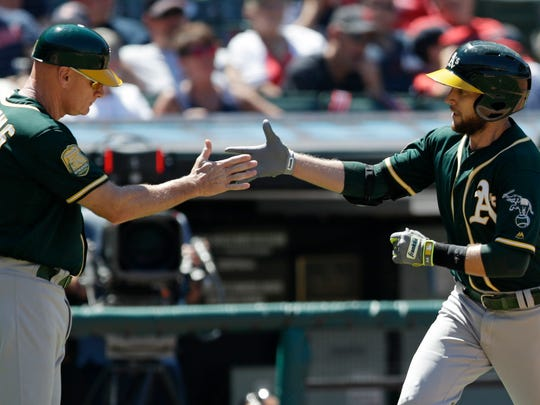 Oakland Athletics third base coach Matt Williams, left congratulates Jed Lowrie after Lowrie hit a solo home run off Cleveland Indians relief pitcher Dan Otero in the seventh inning of a baseball game, Sunday, July 8, 2018, in Cleveland. (AP Photo/Tony Dejak)