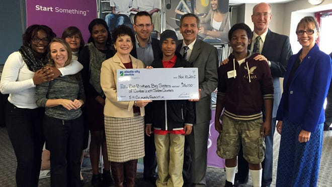 Susan Coan, region vice president for Atlantic City Electric, and Bert Lopez, the utility's public affairs manager, holding a donation check, stand with representatives and participants of Big Brothers Big Sisters of Cumberland & Salem Counties.