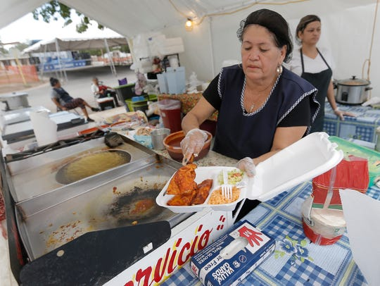 Maria Telles cooks up a plate of enchiladas during
