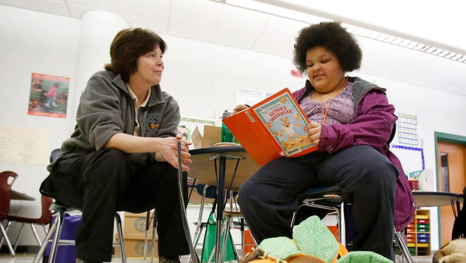 Tiffiney Horsey, 7, reads to Amita, a Kramer Foundation dog, as Julie Lathrop listens Saturday at the Family Reading Partnership of Chemung Valley's Book Fest in Elmira.