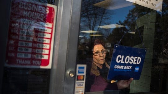 Connie Maglio, owner of Around Again & Again Books closes up her shop Monday afternoon in Wilmington. All nonessential businesses in Delaware will be closed starting at 8 a.m. Tuesday, as ordered Sunday night by Gov. John Carney.