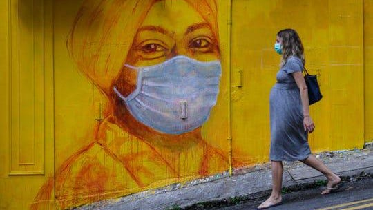 In this file photo taken on March 23, 2020, a pregnant woman wearing a face mask as a precautionary measure walks past a street mural in Hong Kong, on March 23, 2020.