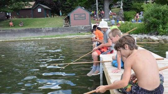 Kids fish off a dock at Camp Stella Maris in Livingston County in the Finger Lakes of New York.