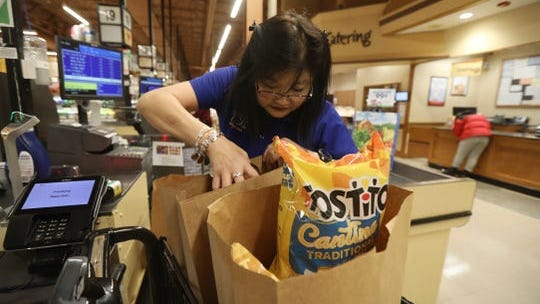 Zoe Kent, front end cashier at the Pittsford Wegmans, packs a customer's groceries in paper bags. Wegmans started their plastic bag ban Jan. 27.