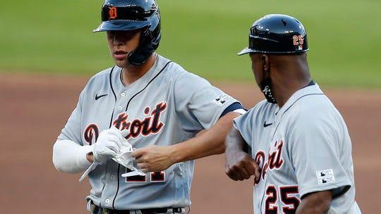 Tigers center fielder JaCoby Jones, left, bumps elbows with first base coach Dave Clark after hitting a single in the third inning against the Cincinnati Reds at Great American Ball Park in downtown Cincinnati on Friday, July 24, 2020.
