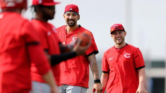 Cincinnati Reds right fielder Nick Castellanos (second from right) and outfielder Mark Payton (right) smile toward director of strength and conditioning Sean Marohn (far left) during conditioning drills, Friday, Feb. 21, 2020, at the baseball team's spring training facility in Goodyear, Ariz.