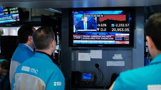 The coronavirus crisis drove the U.S. economy into a recession in February but some economists are holding onto hope that the recession could have ended by May. File photo: As President Trump speaks on March 16, traders work on the floor of the New York Stock Exchange (NYSE). (Photo by Spencer Platt/Getty Images)