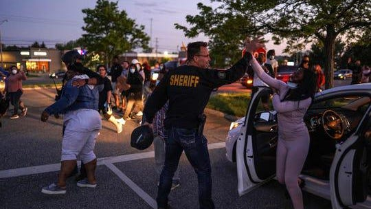 """Genesee County Sheriff Chris Swanson high fives a woman who called his name as he marches with protestors of police brutality and in memory of George Floyd on Saturday, May 30, 2020 in Flint Township. Protestors marched along Miller Rd. In Flint Township before ending up at the Flint Township Police Department Headquarters where they were met by police in riot gear. Swanson deescalated the situation by asking one of the protesters what he wanted of them. They replied to walk with us and so he did with some of his deputies. """"We're on the community's side. Al we had to do was talk to them and now we're walking with them. Everybody wins. The cops in this community, we condemn what happened. That guy's not one of us. You have police officers here that do it everyday for the right reasons. We're asking people just to trust the police. Trust us tonight we're walking with you. We prove it by our actions,"""" Swanson said. """"When I look at that all the good we do in the community across the nation can be destroyed in on act. We were the heroes a week ago so we're going to get back on the hero platform and treat people right. Give people a voice."""""""