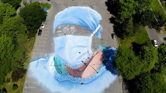 Artist Jorge Rodriguez-Gerada works on a 20,000-square foot mural of a health care worker in a parking lot in Flushing Meadows Corona Park in the Queens borough of New York on May 27, 2020.