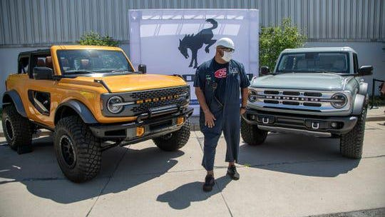 Ford Michigan Assembly Plant in Wayne employee and team leader Eric Robinson poses with the new 2021 2- and 4-door Broncos on Tuesday, July 21, 2020 outside of the plant.